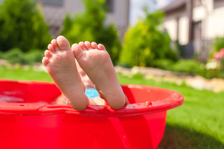 Closeup of little kids legs in small red pool Stock Photo