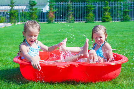 Two little sisters playing and splashing in the pool on a hot sunny day photo