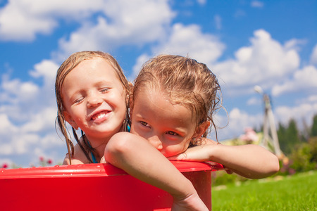 Two cute little happy girls having fun in small pool outdoor on hot summer day photo