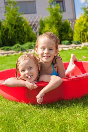 Two little happy girls having fun in small pool outdoor on summer day photo