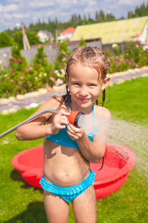 hosepipe: Happy adorable little girl smiling and pouring water from a hose Stock Photo