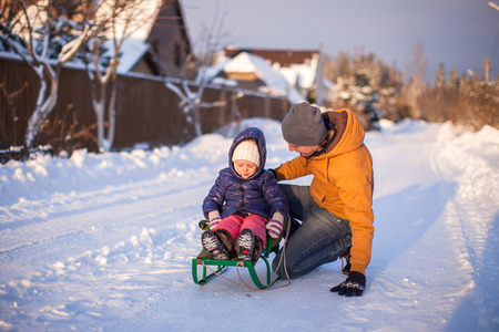 to go sledding: Young dad sledding his little adorable daughter on a sunny winter day