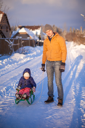 to go sledding: Young dad sledding his little daughter on a sunny winter day