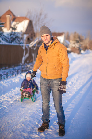 Young father sledding his little daughter on a sled in the snow outdoors photo