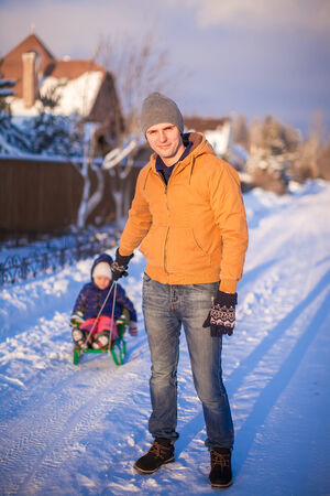 to go sledding: Young dad and little girl go sledding in a cold winter day