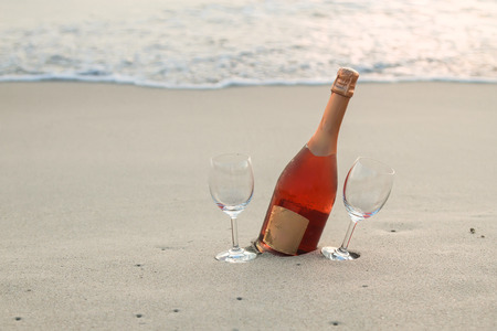 Bottle of red wine and two glasses on the white sandy beach photo