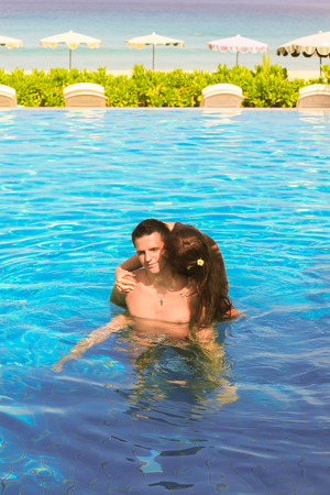 Young loving couple in the swimming pool photo