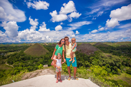 Young family with two girls on a background of the Chocolate Hills in Bohol photo
