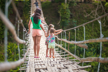 Back view of little girls and young woman walking on suspension bridge over the River Loboc, Philippines