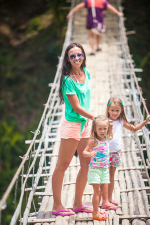 Little girls and young woman walking on suspension bridge over the River Loboc, Philippines photo