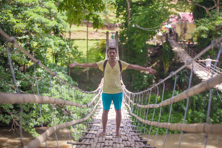 Young guy on the suspension bridge over the River Loboc, Philippines photo