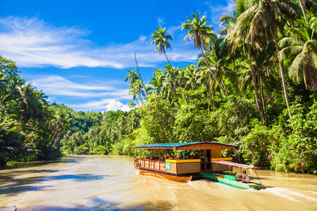 river scape: Exotic cruise boat with tourists on a jungle river Loboc, Bohol