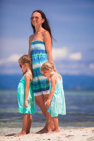 Young mother and her little daughters enjoying summer vacation photo