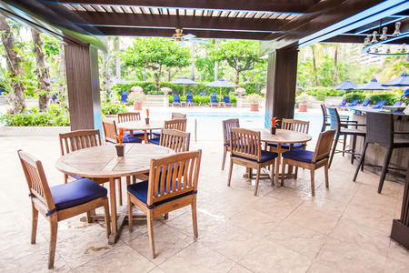 Hotel outdoor cafe with white table and chairs photo