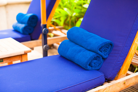 Close-up of towels on the poolside loungers photo