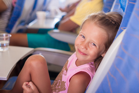 Little smiling happy girl in the airplane photo