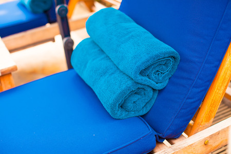 Close-up of towels on the loungers near swimming pool photo