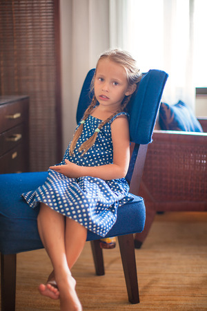 chairs: Portrait of little adorable girl on chair in a hotel room Stock Photo