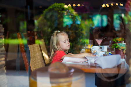 Adorable little girl in a beautiful cafe outside the window photo
