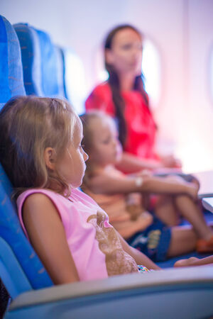 Little girls and young mother in the airplane photo