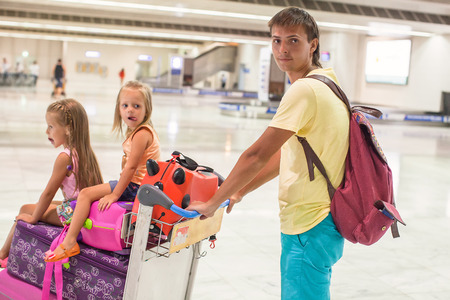Young father and little cute daughters with luggage in airport photo