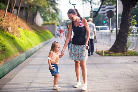 Young mother walking with little girl in a big city outdoor photo