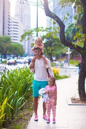 Young father walking with little girls in a big city outdoor