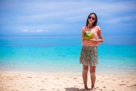 Cute young woman with coconut on tropical beach photo