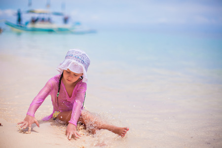 Little cute girl playing in the sand on a hot sunny day photo