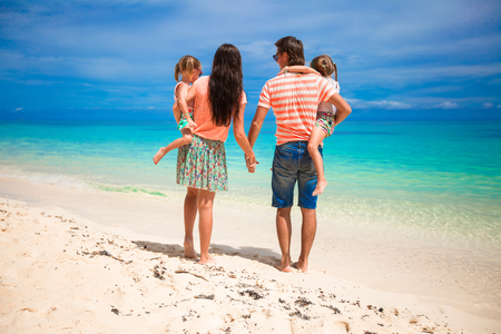 Back view of beautiful family with two daughters at exotic beach on sunny day photo