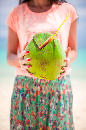 Closeup green big coconut in hands of young woman photo