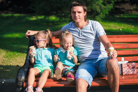 Portrait of two little girls and young father eating ice-cream outdoors photo