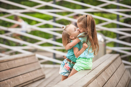 girlie: Two fashion cute sisters go hand in hand in the park Stock Photo