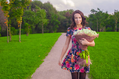 Beautiful young woman with bouquet of roses Stock Photo