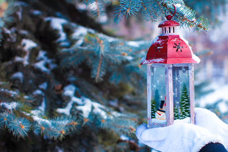 Beautiful vintage Christmas lantern on warm mittens photo