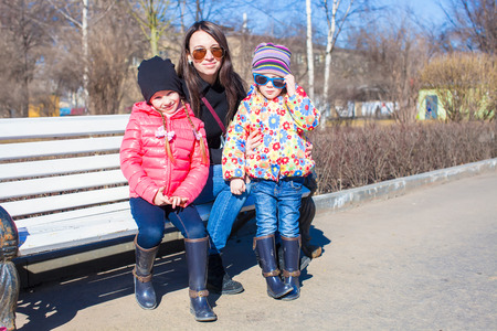 Portrait of young mother and little girls have fun at sunny day outdoors photo