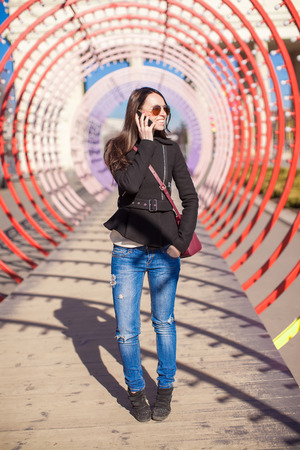 Young happy woman talking on the phone outdoors photo
