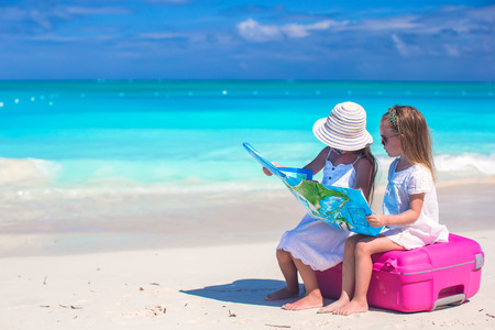 Little girls with big suitcase and a map on tropical beach