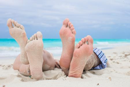 pies masculinos: Cierre de pies masculinos y femeninos en la playa de arena blanca Foto de archivo