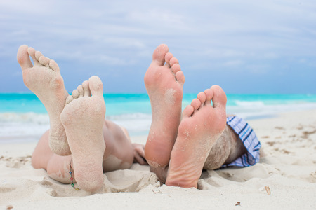 bathing man: Close up male and female feet on white sand beach