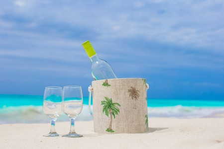 Bottle of wine and two glasses on the white sandy beach photo