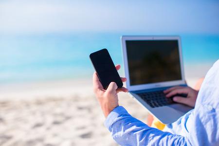 Close up Telefon auf dem Hintergrund der Computer auf dem Strand Standard-Bild - 27824680