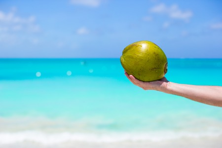 Closeup of coconut in hands against the turquoise sea photo