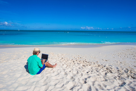 Young man with laptop on the background of turquoise ocean on tropical beach photo