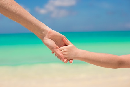 the turks: Close-up hands of mother and kid walking on the beach Stock Photo