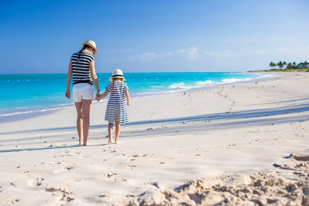 Back view of mother and daughter at Caribbean beach photo