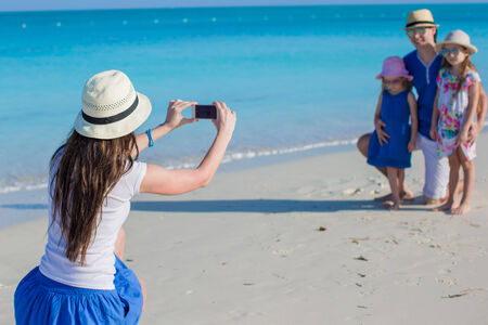 Young mother making photo on phone of her family at tropical beach photo