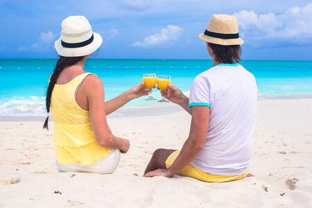 clang: Loving couple with two glasses of orange juice on a tropical beach