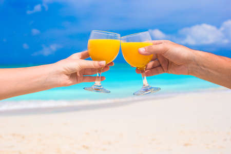 clang: Two hands hold glasses with juice background blue sky