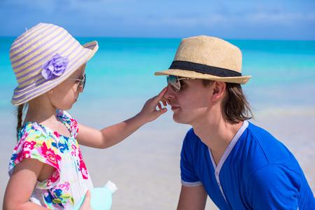 Meisje smeren de papa's neus Sun Protection Cream